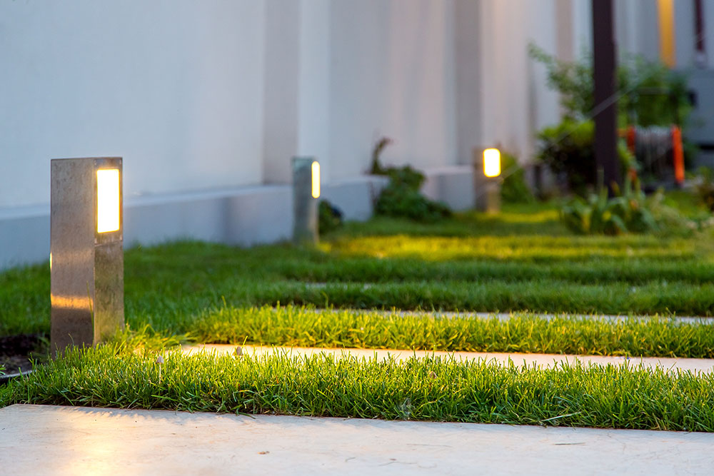 ground lantern lighting marble walkway in the evening park with a green lawn, closeup lantern illumination warm light marble pavement.