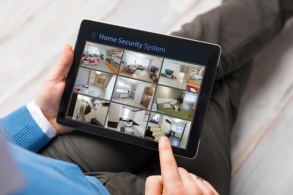 Man looking at home security cameras on tablet computer