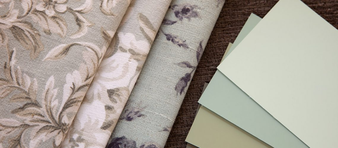 Light green subdued paint color and fabric swatches, floral pattern interior design.